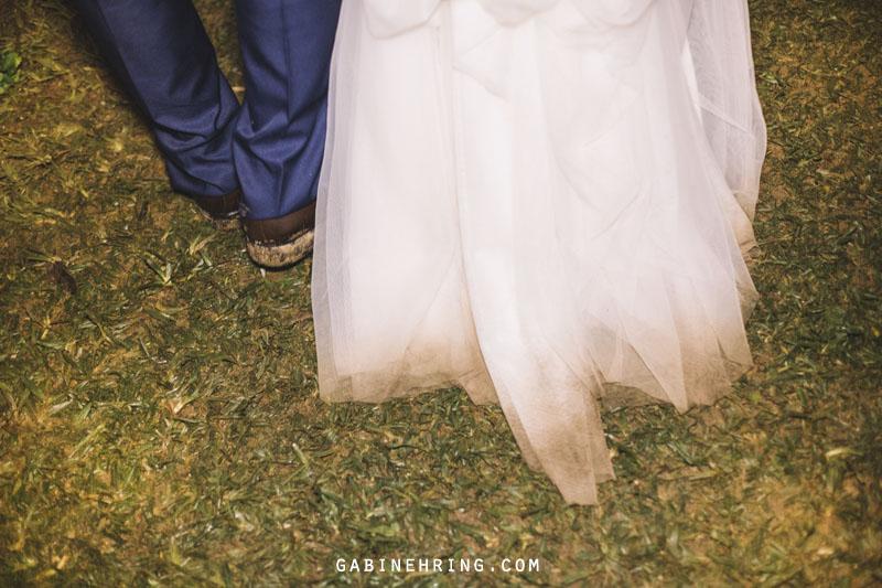 noivos no final da festa de um casamento em casa com a barra do vestido sujo
